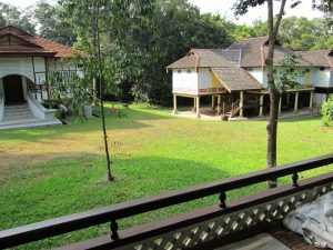 View of two traditional Malay houses and shared lawn from the Rumah Balai wooden verandah