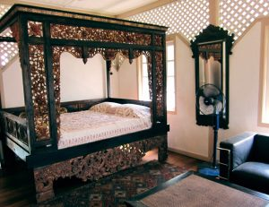 Carved wooden king bed frame and mirror with a carved wooden frame