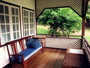 Wooden sofa with blue cushions on the Rumah Balai verandah